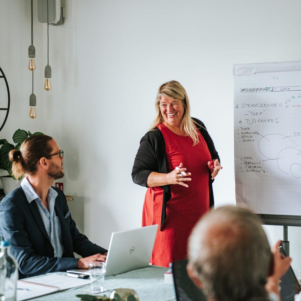 eerste stappen naar een workshop lanceren vrouw legt info flipchart uit