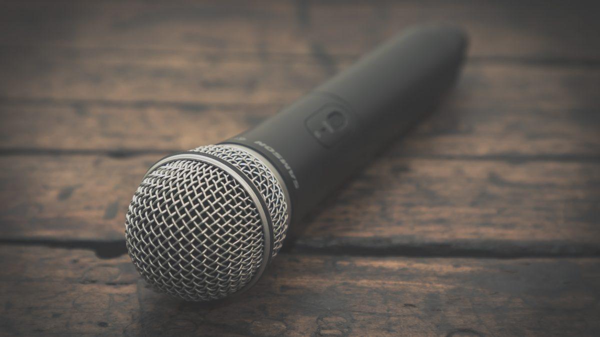 Succesvolle persconferentie organiseren Melkhuisje microfoon op houten tafel