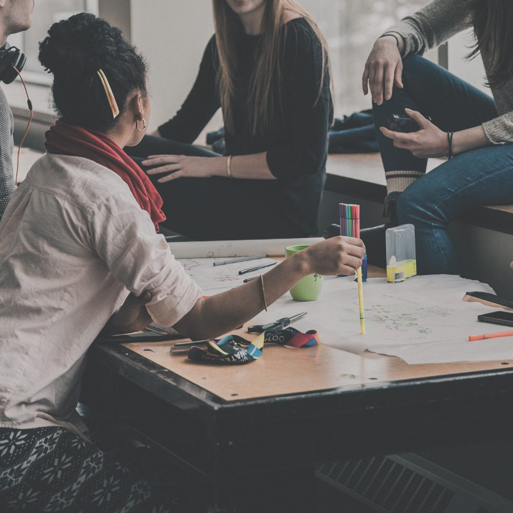 Fysiek contact nodig samenwerkende groep 5 personen zit aan tafel melkhuisje