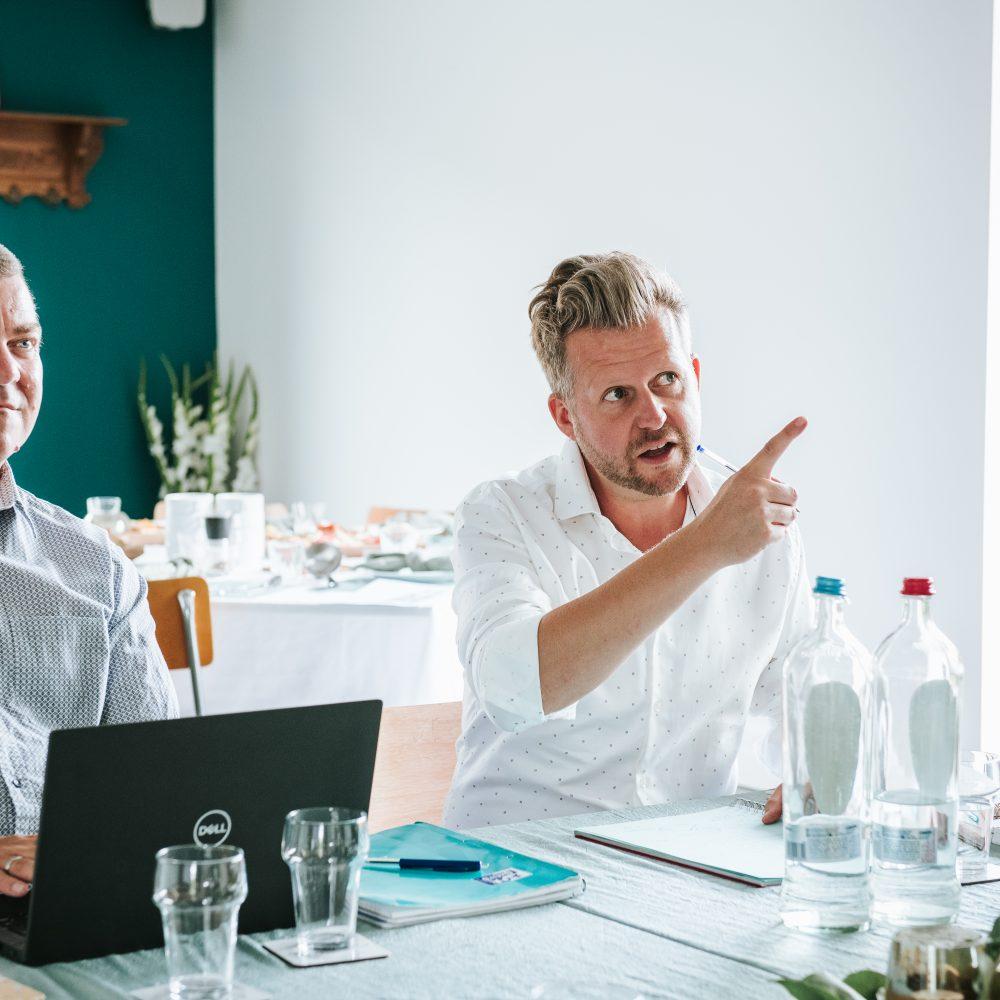 Twee mannen zitten aan tafel achter laptops en vragen wat er gaat veranderen aan vergaderen na corona